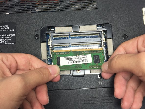 Remove the lower RAM chip from its socket by gently gripping the left and right edges with your fingers and pulling the chip towards your body until it slides completely free of the computer.