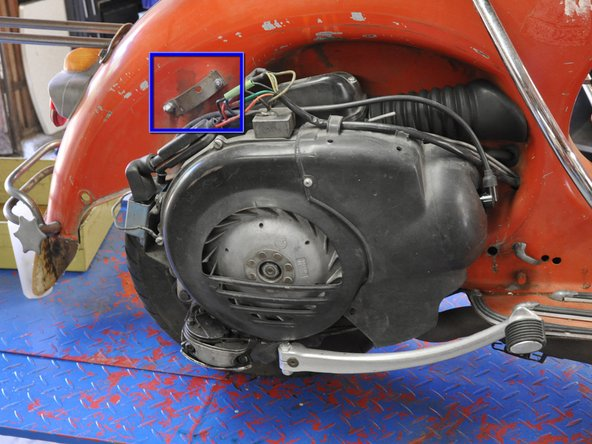 Carefully lift the engine cover up and away from the scooter, mindful of the mounting bracket near the rear of the engine.