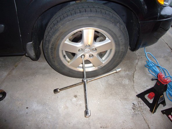 Loosen the lug nuts one half turn while the tire is still on the ground.  A large amount of force may be required and the tire will just rotate if the car is on jackstands.