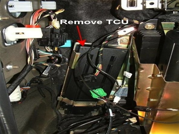 Once the bracket is removed, you will need to remove the phone TCU (Telephone Control Unit).  The TCU is the black, rectangular control module in the rear of the compartment.  This can easily be done by removing the 10 mm mounting screws for your specific BMW phone TCU.