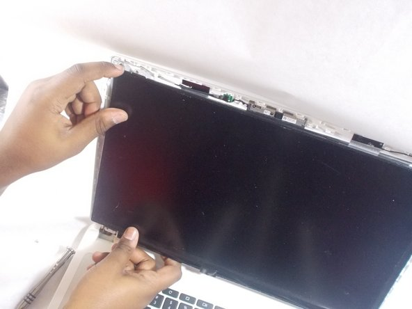 Grab the edges of the screen and pull it out towards you.