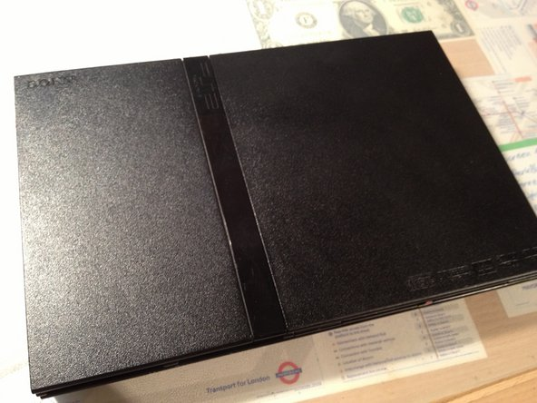 On a flat working surface, flip the PlayStation 2 Slimline so that the bottom side is facing up.