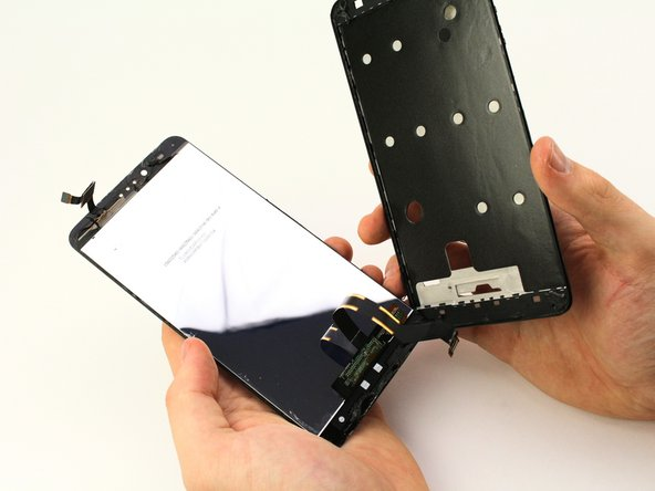 Push the digitizer flex cable through the hole in the frame to separate the LCD from the phone.