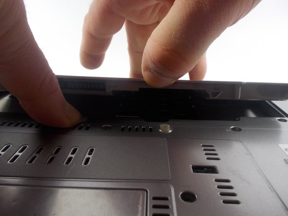 While holding the locking mechanism to the right, insert your finger into the tab and lift up.