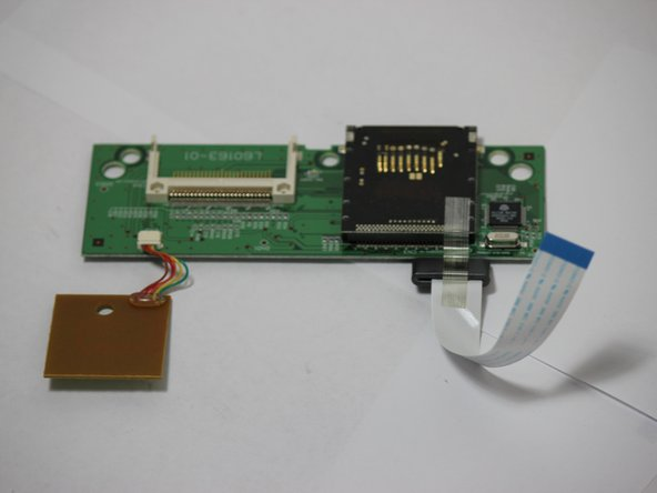 Locate the clear data ribbon with a blue tip that connects the memory card reader to the control panel motherboard