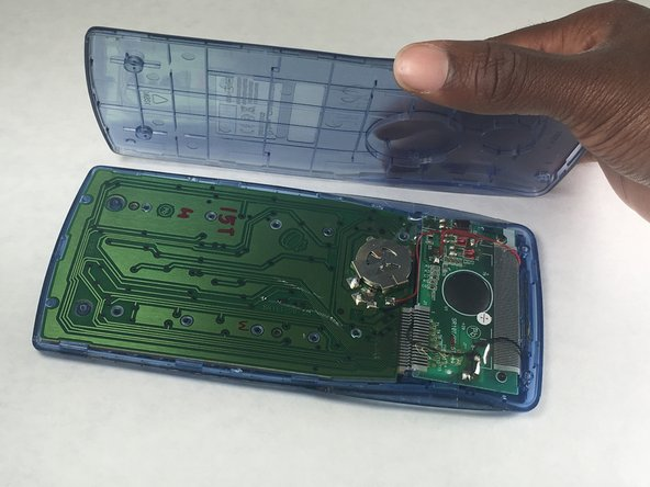 Separate the two panels to reveal the calculator's green circuit board.