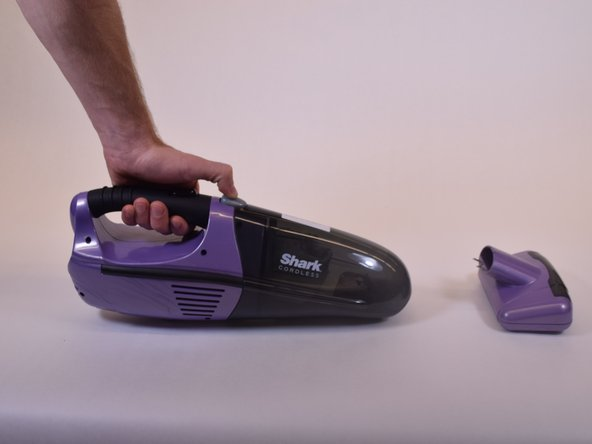 Separate the dust cup by pressing the grey push button on top of the vacuum and pulling it apart from the body.