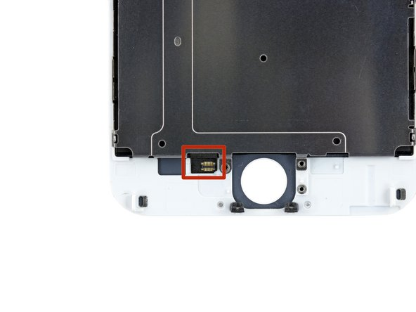 The next step requires peeling one end of the home button cable (highlighted in red in the second picture) that is affixed to the back of the display assembly with strong adhesive. We highly recommend using an iOpener to heat the bottom of the display assembly, directly on top of the home button.