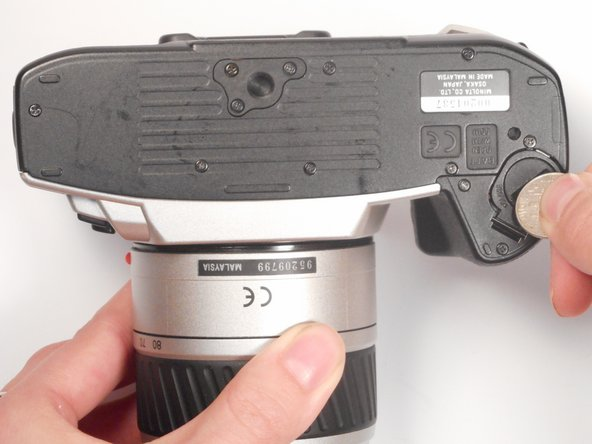 Locate the battery compartment on the bottom panel of the camera.