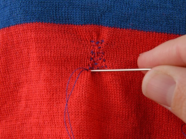 Drive the needle into the bottom corner of your stitching.