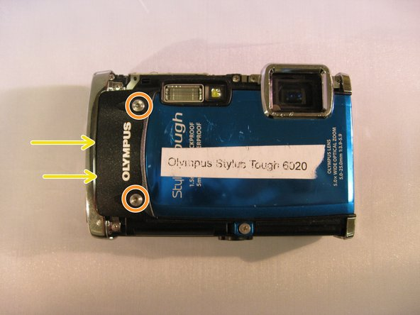 "Using a T6 Torx screwdriver, unscrew the two 3.5mm screws located on the black ""Olympus"" face plate."
