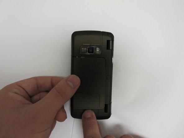 Faites glisser le loquet de dégagement vers le bas et vers vous tout en soulevant le côté gauche du couvercle de la batterie.
