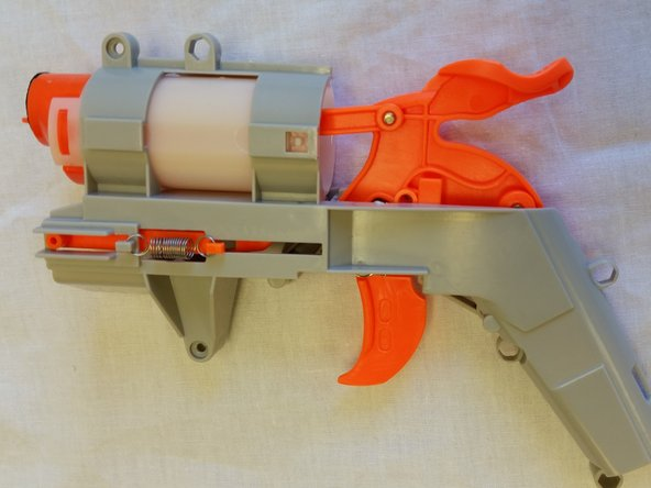 Remove the exterior spring from the sliding mechanism and rotate the gun to the opposite side.