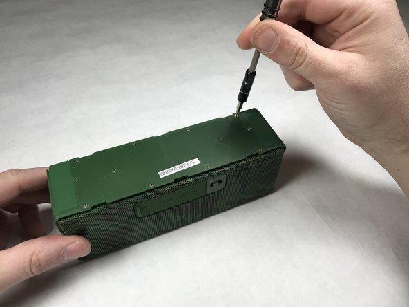 Using a Phillips #0 screwdriver, remove the the ten 5.1mm screws that hold down the battery panel on the bottom of the speaker unit.