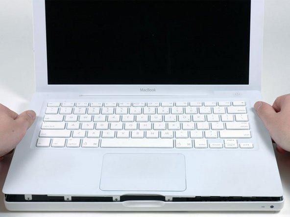 天板のキーボードおよびトラックパッドはリボンケーブルでロジックボードと接続されているため、まだ絶対に無理やり引き抜こうとしないでください。リボンケーブルが切れてしまうおそれがあります。