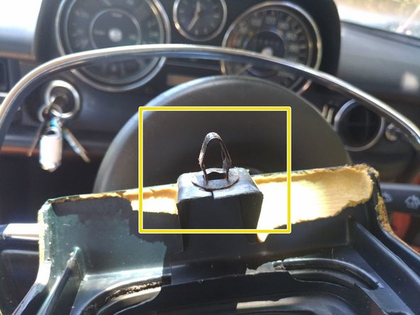 There is a simple metal trim clip holding the rear of the centre-console trim panel down (marked by a yellow box in photo 2)