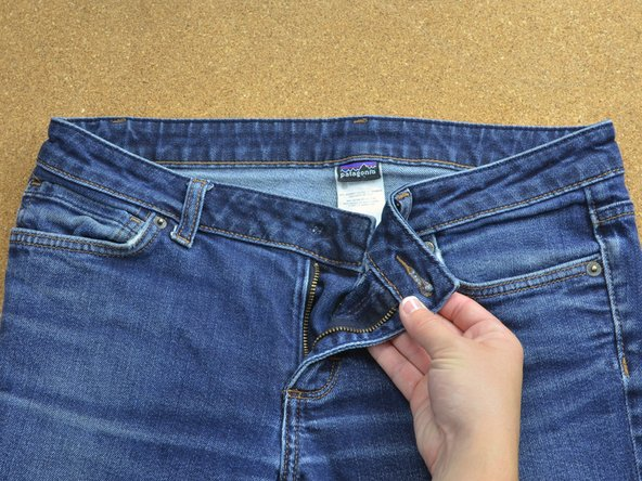 Unzip the fly and open the jeans at the waistband to reveal the hole where the button is missing.