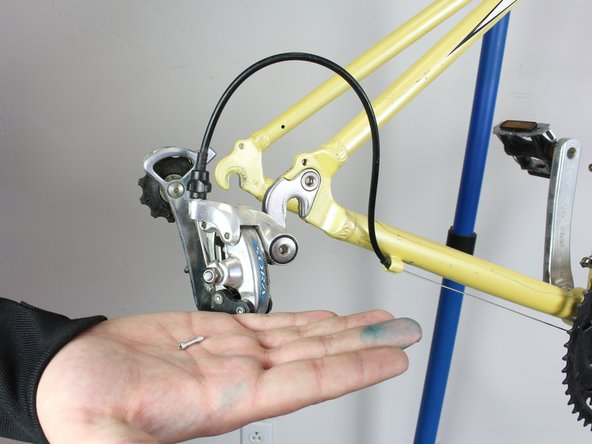 Using a pair of wire cutters, locate the end of the derailleur cable. Cut the wire just below the cap, cutting off the metal end piece.