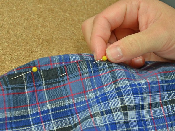 Image 3/3: Pin the two layers together. Be sure to catch only the two layers of fabric you wish to sew back together.