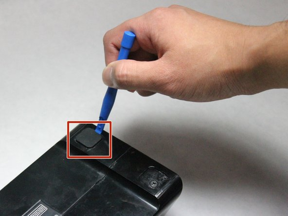 Use the plastic opening tool to remove the four rubber pads from the bottom of the device.
