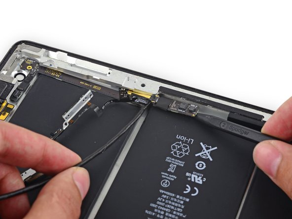 Image 2/3: Pull the board up and out of the space between the battery and the rear case bezel.