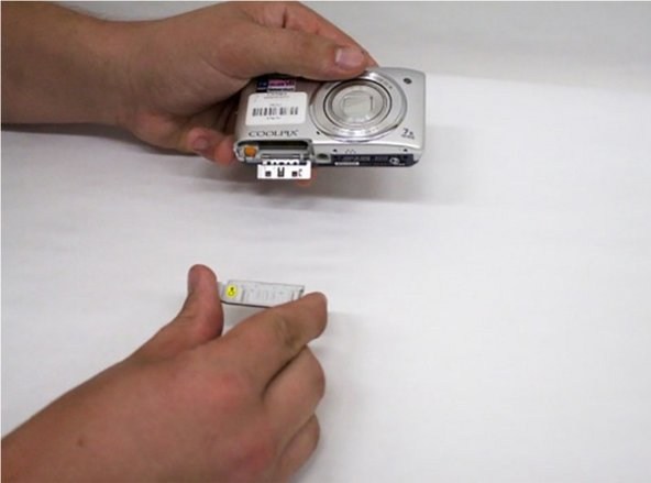 Image 1/1: Using your free hand, pick up your new battery door.