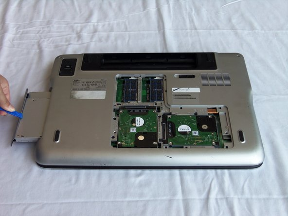 Using a plastic opening tool, pull out the optical drive.