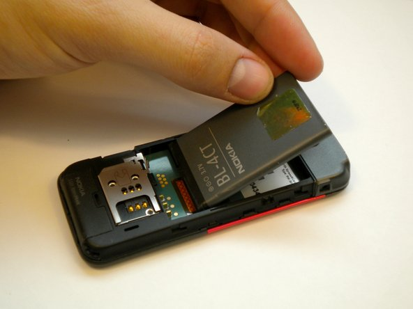 Gently lift the battery with a fingernail and remove it from its housing.