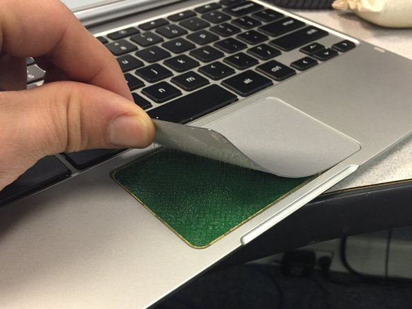 Apply pressure to the the bottom of the Chromebook under the track pad.