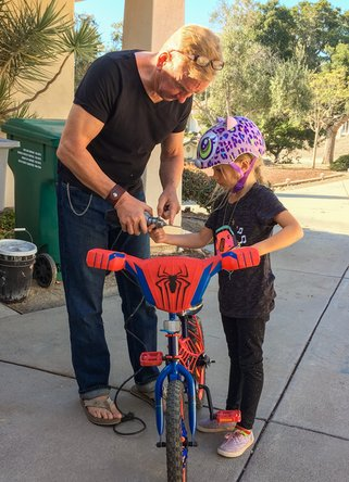 Father fixing his daughter's bike