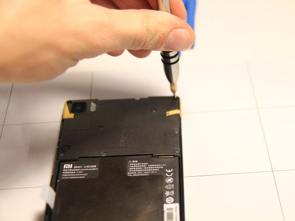 One of the screws is located under an orange sticker at the top right corner of the panel. The sticker can be removed with a pair of tweezers.