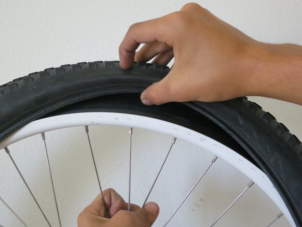 Using one hand to hold the rim, use the other to push one side of the tire back onto the rim.