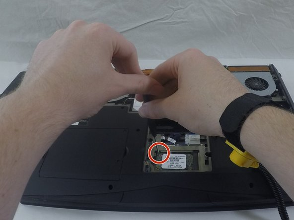 Image 1/2: Remove the small screw on the upper left of the hard drive.