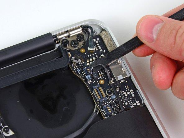 Heble mit dem flachen Ende eines Spudgers den Kabelstecker des  linken Lautsprechers nach oben und aus der Fassung auf der I/O Blende heraus.