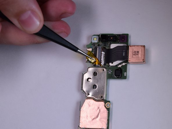 Using the pointed tweezers, remove the tape that covers the ZIF connector.
