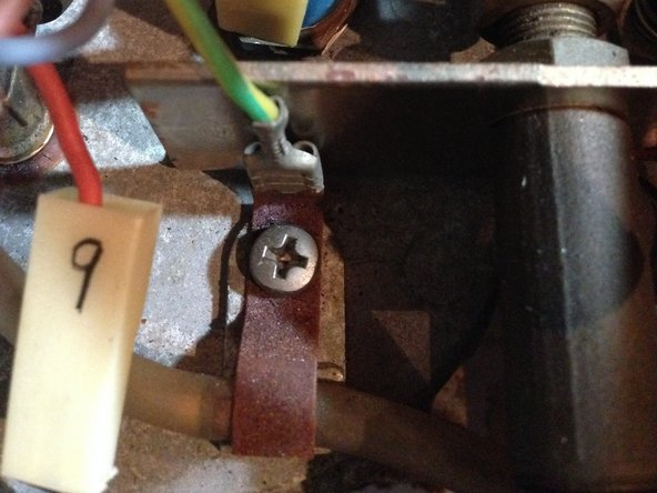 Image 3/3: Next, unscrew the tab securing the grounding wire and the water hose to the top of the boiler.