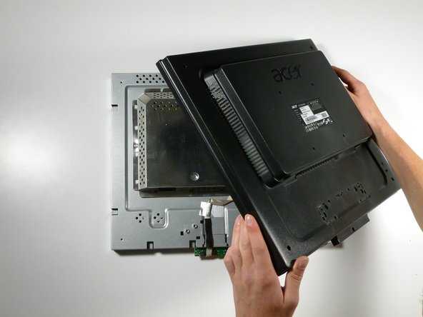 Grab the corners of the monitor and jiggle them upwards to detach the back cover from the inside of the monitor.