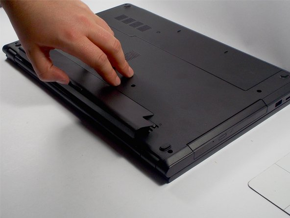 Lift the battery at an angle using your fingertips and remove it from the laptop.
