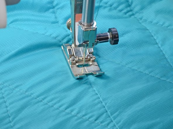 Sink the needle, being sure that it aligns with the stitching.