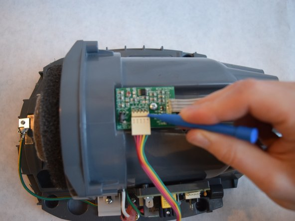 Remove the rainbow ribbon cable from the middle circuit board, using a plastic opening tool.