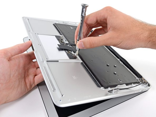 Image 1/3: As in most other unibody MacBooks, the Air's trackpad is held to the upper case with six tiny Phillips screws and comes out without much hassle.