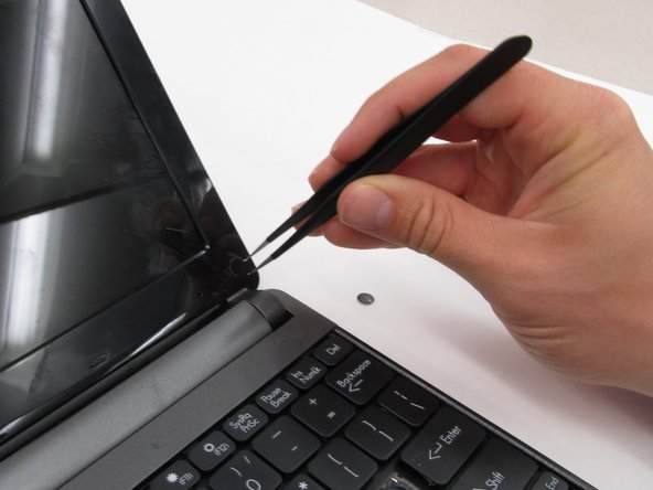 Remove the two screw covers at the bottom right and left corners of the screen using tweezers.