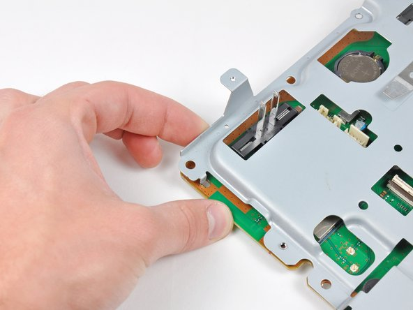 Image 2/2: Gently press the board away from the top shield assembly near the fan connector and the corner of the board near the wireless sockets.