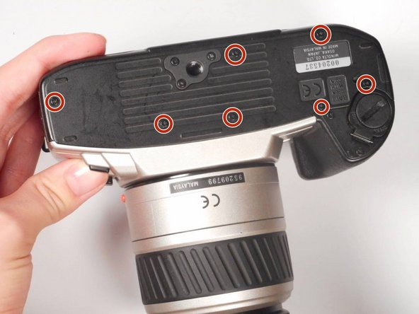 With a screwdriver, remove the (7) black Phillips #00 5mm screws on the bottom of the camera.