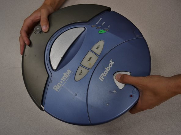 To open the dust bin, grasp the bumper of the Roomba with one hand while using your other hand and thumb to hold the dust bin and press the gumdrop shaped button.