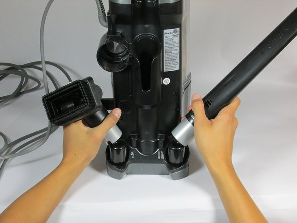 The back of the vacuum has slots to hold up to two vacuum attachments. To store, simply place the attachment onto the circular slots.