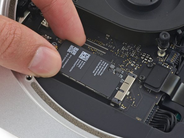 Pull the AirPort card straight out of its socket on the logic board and remove it from the Mac Mini.