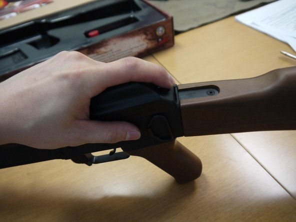 Start by pressing the top cover retainer button and lifting the top cover off of the gun.