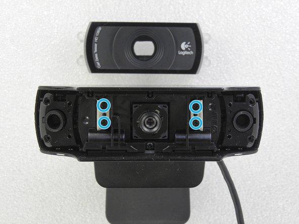 Remova a tampa cristalina da lente. Remova os quatro parafusos philips do suporte de metal. Remova as borrachas dos dois microfones (uma de cada lado).