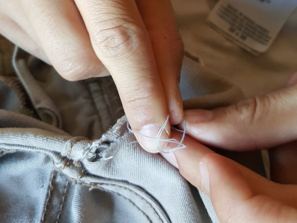 Pull needle and thread through pants  until there is only 2 inches of thread left.
